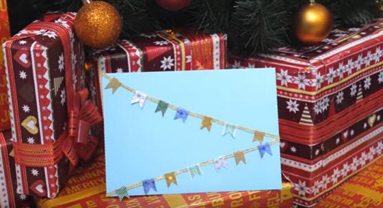 Новогодняя открытка голубого цвета с гирляндами на фоне упаковок с подарками