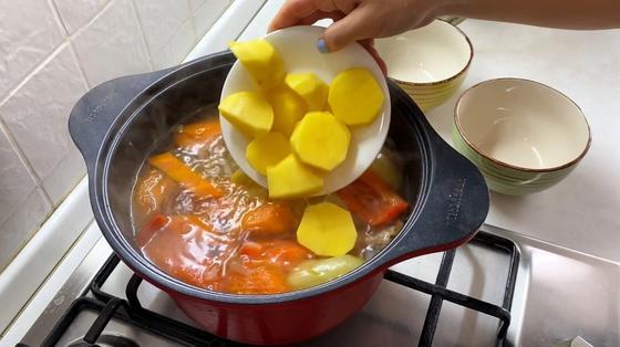 Добавление картошка в кастрюлю с бульоном