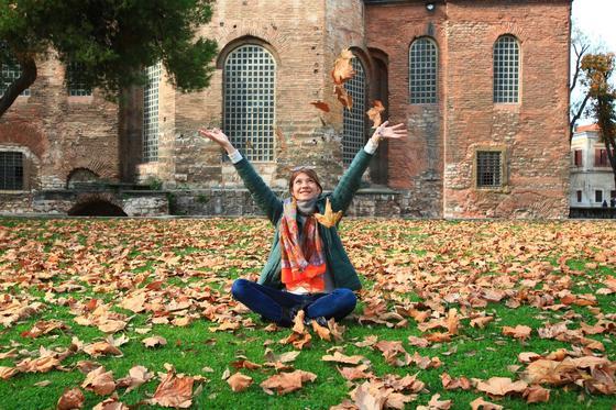 Девушка рассыпает листья на фоне здания
