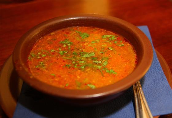Суп харчо с томатной пастой в коричневой тарелке на столе
