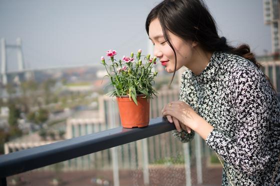Девушка нюхает цветы в горшке