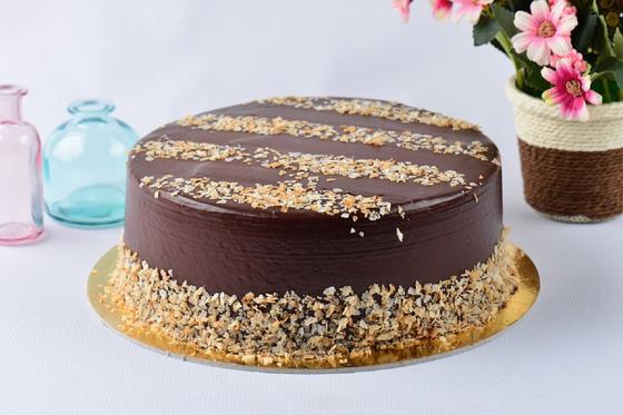 Шоколадный торт, покрытый глазурью и украшенный ореховой крошкой