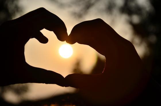 Сердце, сложенное с помощью рук, на фоне Солнца
