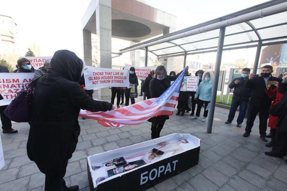 Люди накрывают гроб американским флагом