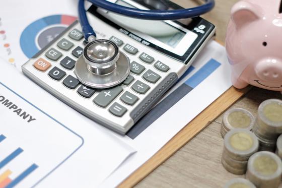 Медицинские инструменты лежат с калькулятором и деньгами