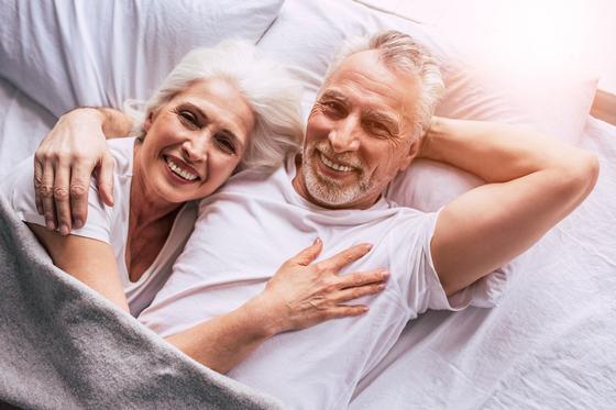 Пожилая пара лежит в кровати