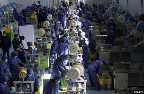 Эштехард қаласындағы медициналық маска шығаратын кәсіпорын жұмысшылары. Фото: EPA-EFE