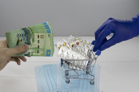 Один человек потягивает деньги, а другой подкатывает маленькую тележку с лекарствами