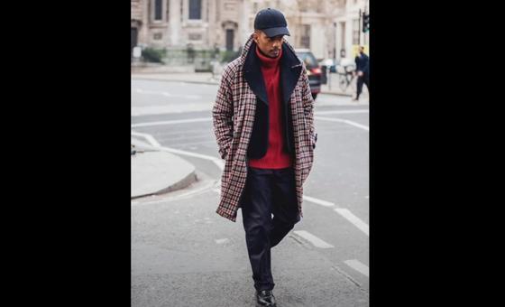 Мужчина в клетчатом пальто идет по дороге