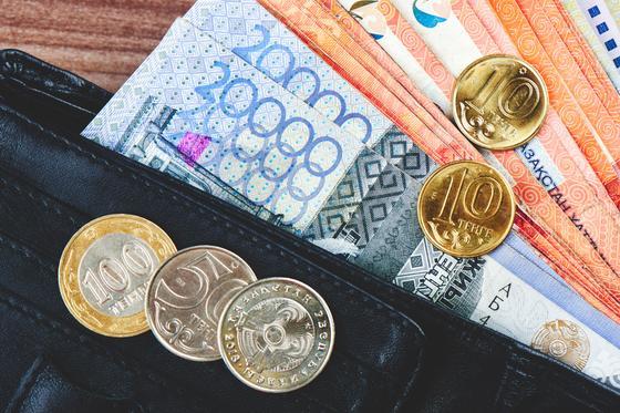 Купюры и монеты тенге лежат в кошельке и на кошельке