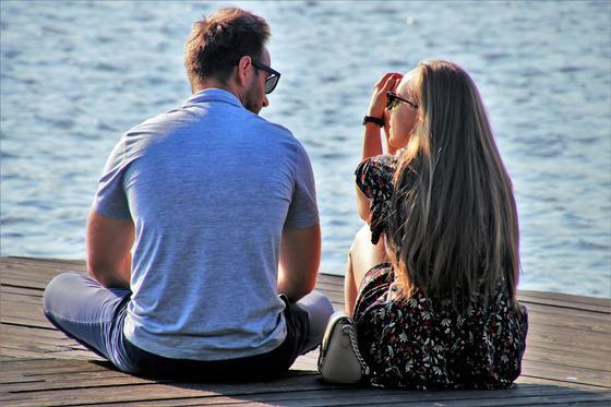 Пара разговаривает сидя на причале