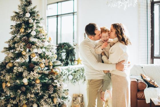 семья обнимается возле новогодней елки