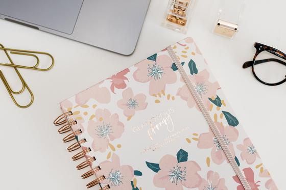 ежедневник с цветами и канцелярия на столе