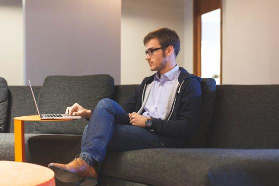 Парень сидит на диване и смотрит в ноутбук