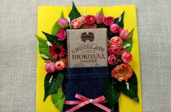 Открытка из кармана джинсов, розовых бутонов и шоколадки