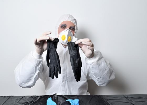 Женщина в респираторе держит резиновые перчатки