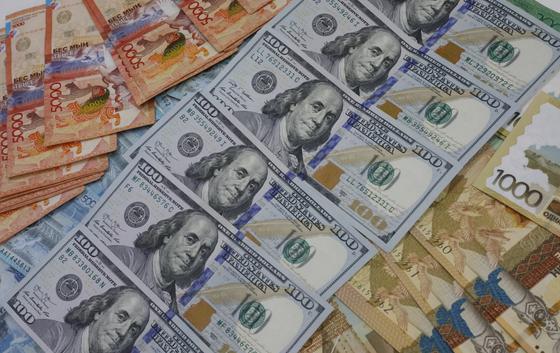 Долларовые купюры лежат среди тенге