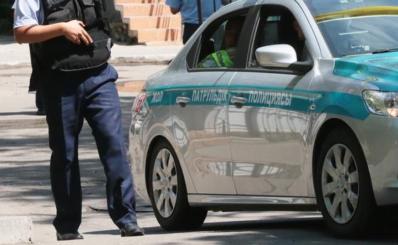 Полицейский стоит возле патрульной машины