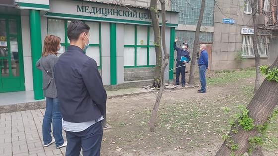 Люди стоят возле медцентра