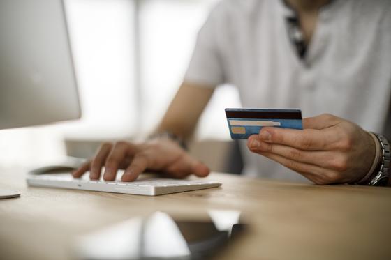 Человек набирает текст на клавиатуре с пластиковой картой в левой руке