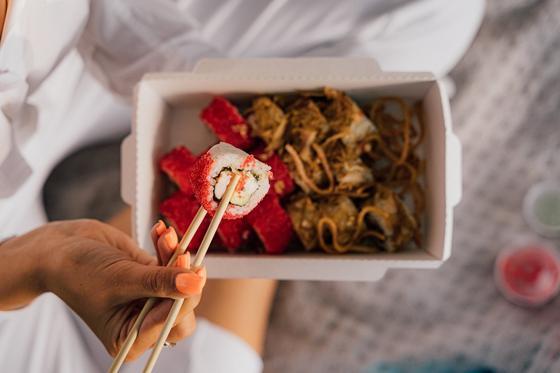 Женская рука держит китайские палочки с ролом над коробкой восточных деликатесов