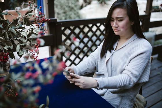 Плачущая девушка сидит за столом на открытой террасе и смотрит на экран телефона