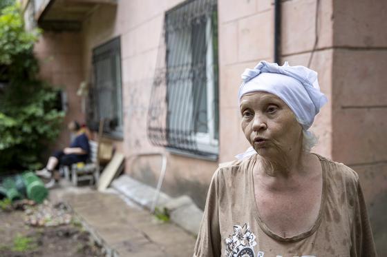 Женщина стоит возле дома