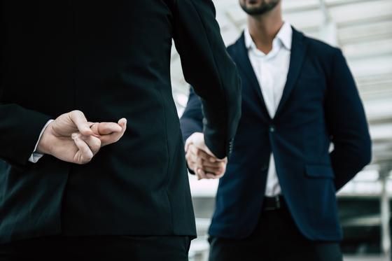Мужчина в деловом костюме заключает договор, который не собирается исполнять