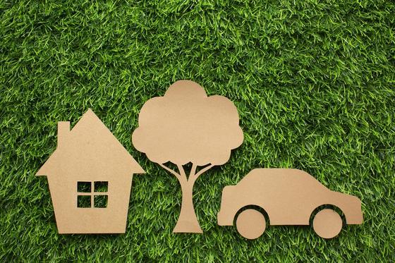 Значки машины и дома из картона лежат на траве