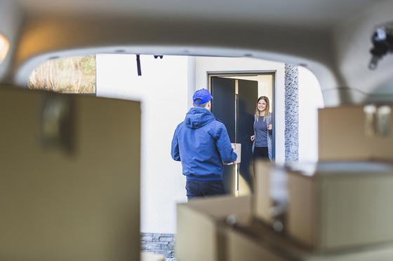 Доставщик товаров стоит у двери дома