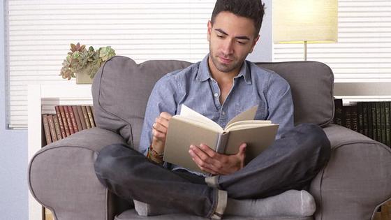Мужчина, сидя на диване, читает