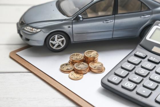 Модель машины на фоне калькулятора и монет