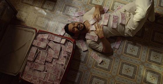 Мужчина лежит на полу рядом с чемоданом денег. Кадр из фильма «Чемодан удачи»