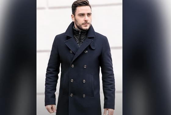 Мужчина в пальто в стиле милитари стоит у стены