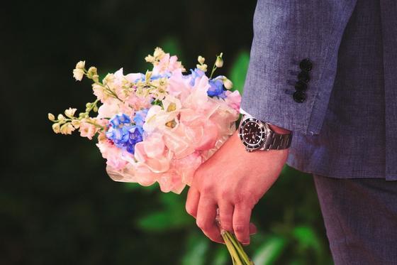 Мужчина держит в руке букет цветов