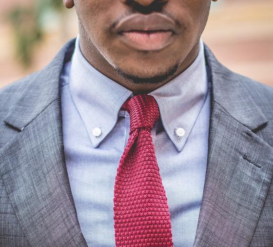 Мужчина в сером пиджаке и красном галстуке