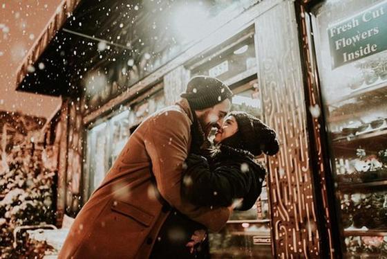 Влюбленные парень и девушка на улице под снегом