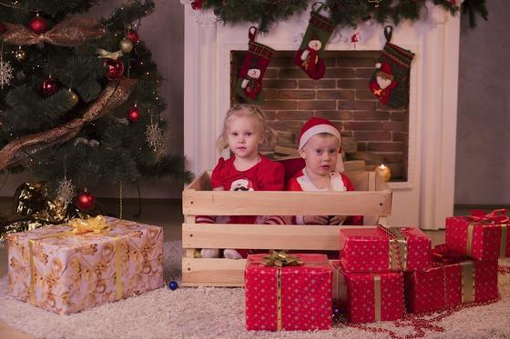 Мальчик и девочка возле камина и новогодней елки