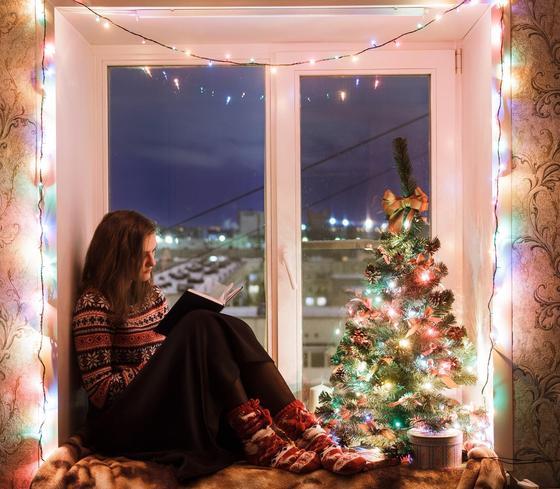 Девушка читает, сидя на украшенном к Новому году подоконнике