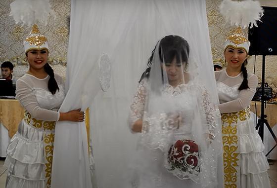 Невеста в окружении девушек в национальных костюмах