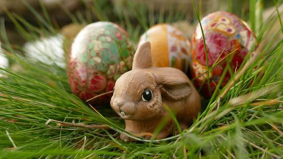 Фигурка кролика рядом с крашеными яйцами в траве