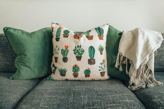 Цветные подушки и плед на диване с серо-зеленой обивкой