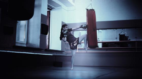 Девушка бьет по боксерской груше