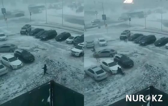 Человека в Астане снесло диким ветром и бросило на машину (видео)