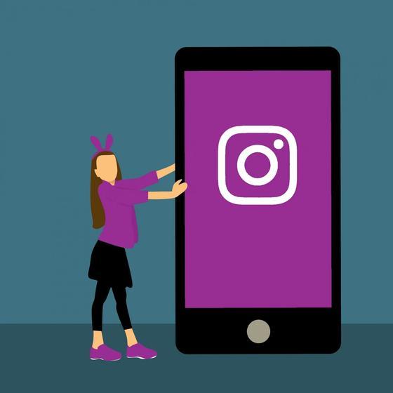 Девушка двигает телефон со значком Instagram