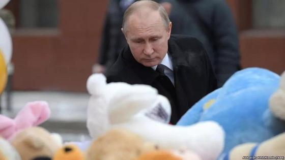 Путин сауда орталығындағы өрттен қаза тапқандарды еске алатын орынға гүл қойып тұр. Фото: Азаттық