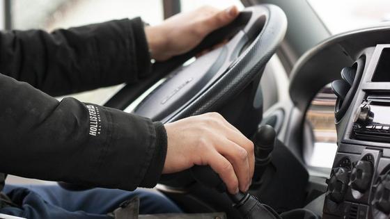 Водитель держит руль