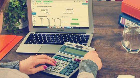Девушка сидит за столом с ноутбуком и калькулятором