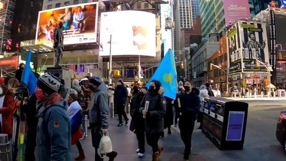 Люди несут в руках флаг Казахстана