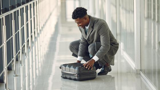 Мужчина в костюме проверяет чемодан